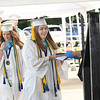 Principal Lori Knight, of Liberty, right, hands Mallory Brown, salutatorian, her diploma in front of the High School Friday morning. Parents stayed in their vehicles and drove their graduates up to a designated area where they were able to get out in groups of 10 to control the setting of no more than 25 individuals gathering at once. Parents were able to hear speeches through their radio by tuning into 107.7 The River.<br /> (Rick Barbero/The Register-Herald)