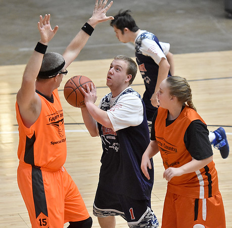 (Brad Davis/The Register-Herald) Raleigh County's Matt Slone drives and shoots as Fayette County's Steven Bragg defends during the Special Olympics game at the New River Community and Technical College Shootout Saturday morning at the Beckley-Raleigh County Convention Center.