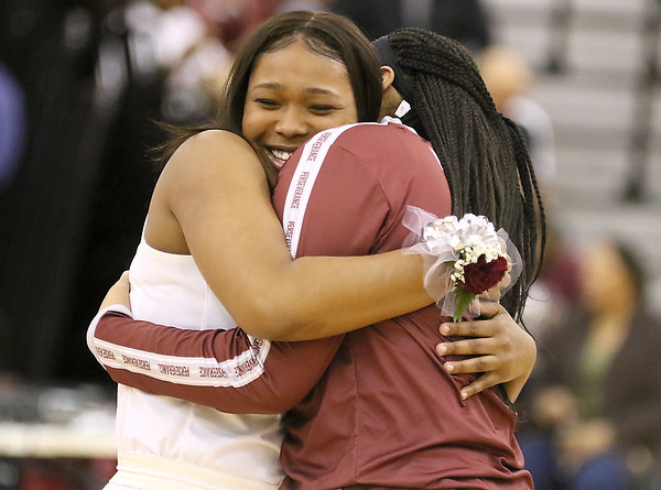 (Brad Davis/The Register-Herald) Woodrow Wilson senior player Victoria Staunton, left, gets a big hug from teammate Jamara Walton following Senior Night festivities prior to the Lady Flying Eagles' game against South Charleston Wednesday night in Beckley.