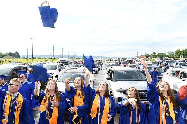 Seniors of Greenbrier West High School making speeches toss their hats up during the graduation ceremony Friday evening  held at the State Fair of West Virginia's free parking lot in Fairlea. <br /> (Rick Barbero/The Register-Herald)