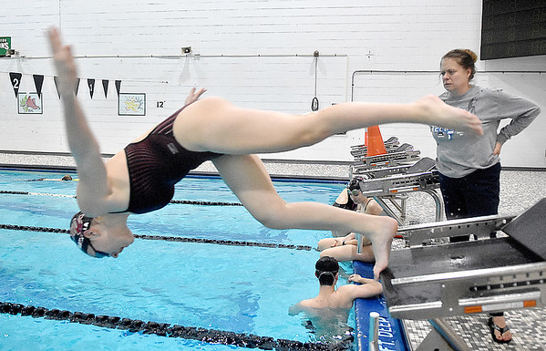 (Brad Davis/The Register-Herald) Head coach Robin Feldhake, right, looks on as swimmer Ashlee Mainella (jumping) and teammates work on starts during Flying Eagles swimming practice Friday afternoon at the YMCA of Southern West Virginia.