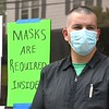 Tony Evans, owner of Flat Top Fridays on Court Street in Fayetteville, waits outside his business for one of his appointments. Evans said he opened back up this past Mondy and requires everyone to wear a mask before entering his shop.<br /> (Rick Barbero/The Register-Herald)