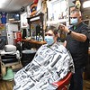 Tony Evans, owner of Flat Top Fridays on Court Street in Fayetteville, right, cuts Kristen Clunch, of Oak Hill hair Thursday afternoon.  Evans said he opened back up this past Mondy and requires everyone to wear a mask before entering.<br /> (Rick Barbero/The Register-Herald)