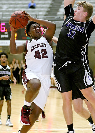 (Brad Davis/The Register-Herald) Woodrow Wilson's Mykel McDowell drives to the basket as Riverside's Alec Hess defends Wednesday night at the Beckley-Raleigh County Convention Center.