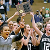 (Brad Davis/The Register-Herald) Westside players celebrate with the trophy after defeating Wyoming East for the Region 3, Section 1 championship Wednesday night in New Richmond.