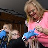 Mary Roop, helps put rubber gloves on Mila and Aspen roop to celbrate their sister Charlee's first birthday held in the driveway off of Grandview Road in Beaver Saturday afternoon because of COVID-19. <br /> (Rick Barbero/The Register-Herald)