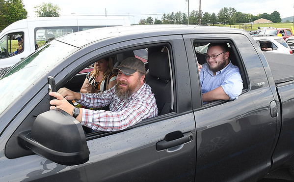 John Lively, father of Reegan Lively, phortographs his daughter making a speech during Greenbrier West High School graduation ceremony Friday evening  held at the State Fair of West Virginia's free parking lot in Fairlea. Sitting in back seat is Reegan's boyfriend Steven Alderson.<br /> (Rick Barbero/The Register-Herald)