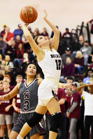 Woodrow Wilson's Cloey Frantz (12) scores a layup over George Washington's Vivican Ho (3) during their Class AAA, Region Conference Final in Beckley on Tuesday. (Chris Jackson/The Register-Herald)