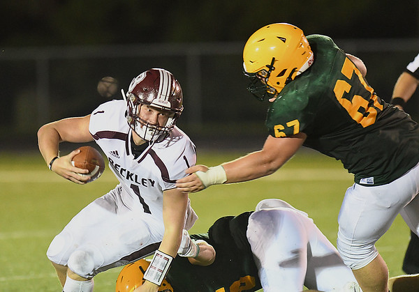 Maddex McMillen, of Woodrow Wilson, left, gets sacked by J.T. Spencer, of Greenbrier East during first half action in Fairlea.<br /> (Rick Barbero/The Register-Herald)