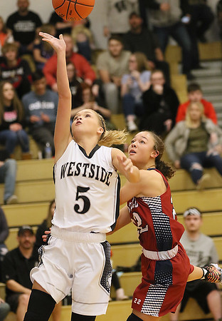 (Brad Davis/The Register-Herald) Westside's Riana Kenneda drives and scores as Bluefield's Jaisah Smith defends Thursday night in Clear Fork.