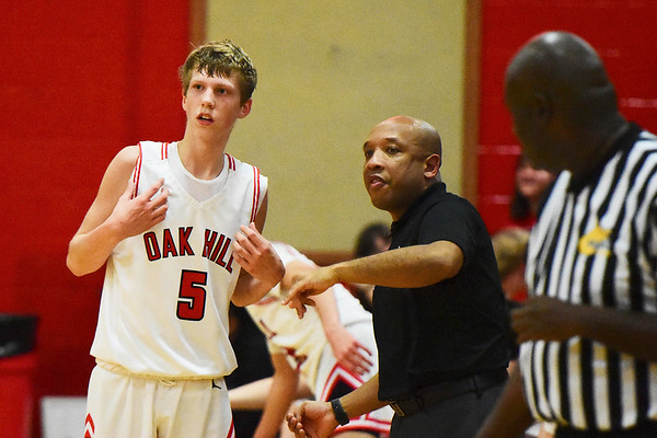 Oak Hill head coach speaks with Samuel Crist during the first half of their basketball game against Liberty  in Oak Hill on Tuesday. (Chris Jackson/The Register-Herald)