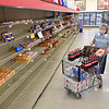 Janet Rollins, looking for a loaf of bread at Goodson's Supermarket on Valley Drive in Oceana Wednesday, was one of ten shoppers allowed in the store because of the coroanvirus crisis caused the Health Department on Tuesday reducing the number shoppers to only10 at a time. Goodson's supplied their employees each with face masks and most chosed to wear them and they also offered to shop for their customers avoiding long wait times to enter the store.<br /> (Rick Barbero/The Register-Herald)