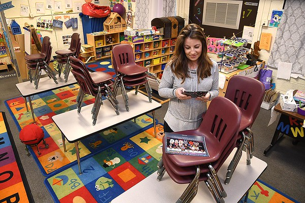 Shannon Wooton, pre-school teacher at Crescent Elementary School. copies a group photo of her class to share with her students on the schools Facebook page.<br /> (Rick Barbero/The Register-Herald)