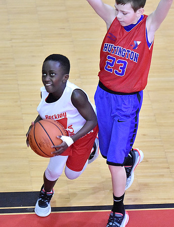 (Brad Davis/The Register-Herald) Beckley YMCA's Ian Asamoah drives to the basket as Huntington's Carter Wolfe defends during 5th Grade Roundball Classic action Saturday afternoon at the YMCA of Southern West Virginia. Huntington won the game.