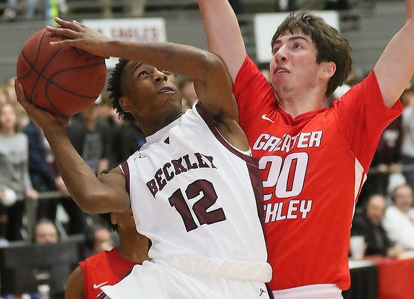 (Brad Davis/The Register-Herald) Woodrow Wilson's Tauvea Davis drives and scores as Greater Beckley's Thaddaeus Jordan defends Friday night at the Beckley-Raleigh County Convention Center.