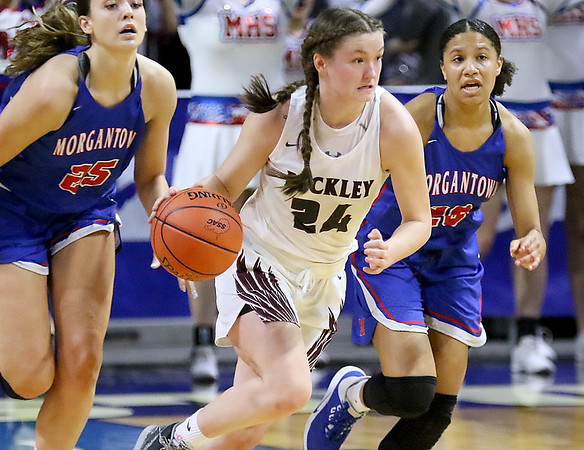 (Brad Davis/The Register-Herald) Woodrow Wilson's Liz Cadle drives up the court as Morgantown's Kaitlyn Ammons, left, and Alayjah Jones persue during Girls State Basketball Tournament Wednesday afternoon in Charleston.