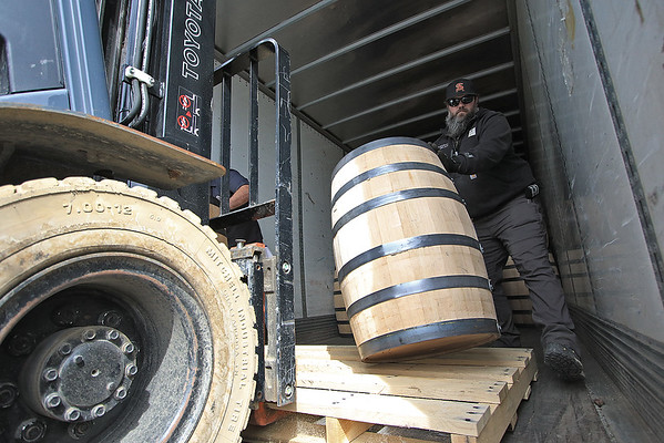 A Smooth Ambler Spirits employee moves West Virginia Great Barrel Company barrels off a truck from the Monday in Maxwelton. The first truckload of 53-gallon whiskey barrels made their way from the company and were delivered to Smooth Ambler Spirits Monday. (Jenny Harnish/The Register-Herald)
