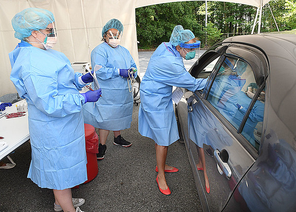 Sarah Frame, medical assistant, left, Adriana Gonzalex, medical assistant, watch Marine Moose, nurse practioner, all with Beckley ARH Hospital, give a COVID-19 test behind the Southern WV Clincic on Stanaford Road in Beckley. Testing is offered Monday through Friday 10 am to 2 p.m. with no out of pocket expense, just need to bring your insurance and results will be back in 2-3 days. The hospital is currently averaging 100 plus test per day.<br /> (Rick Barbero/The Register-Herald)