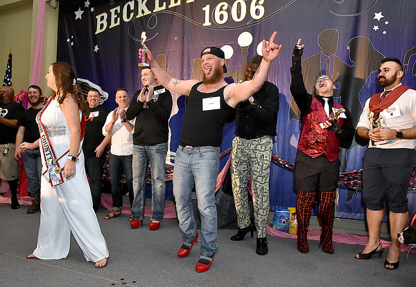 """(Brad Davis/The Register-Herald) Eric Bragg reacts after earning a trophy during the Hunks in Heels """"Fur"""" Real fundraising event Friday night at the Beckley Moose Lodge."""