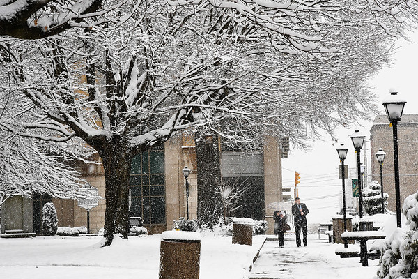 Two people walking down Heber Street in Beckley Tuesday afternoon through a winter wonderland in Shoemaker Square.<br /> (Rick Barbero/The Register-Herald)