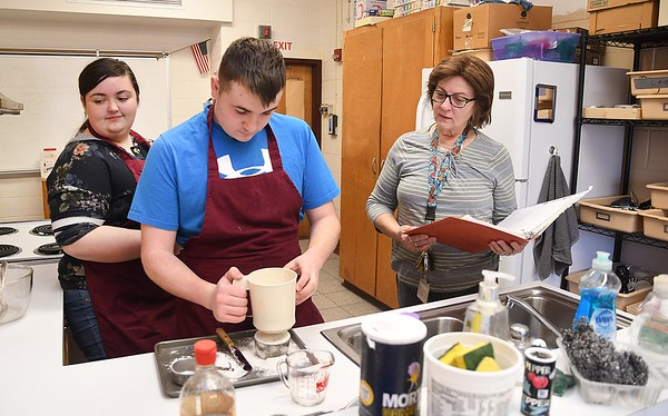 """Linda Shirley, right, baking & pastry and food & nutrition instructor at Woodrow Wilson High School, working with her students, Hannah Shufflebarger and Thomas Stafford, sifting flower to add air and leveling for the proper amount. Senate Bill 297 would require the West Board of Education to create a home economics course for students in secondary school. If passed the class will be called, """"family and consumer science.<br /> (Rick Barbero/The Register-Herald)"""