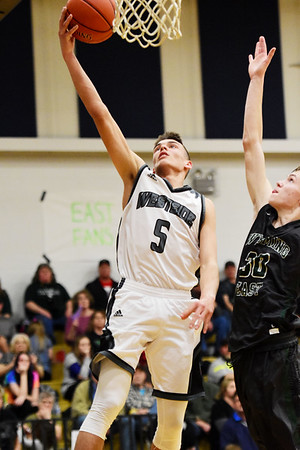Westside's Ethan Blackburn (5) puts a layup up over Wyoming East's (30) during the first half of their basketball game in Clear Fork on Tuesday. (Chris Jackson/The Register-Herald)