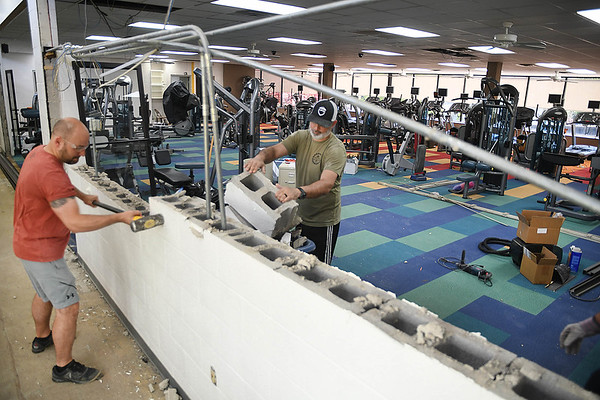 Ryan Gilkerson, membership and wellness director, left, and Jason Logan, sports and recreation director for YMCA in Beckley, tear apart a wall to expand the Wellness Center.<br /> (Rick Barbero/The Register-Herald)