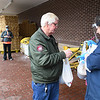 Cecil Lane, of Glen Fork, left, pays for his groceries to Rhonda Martin, who shopped for him while he waited in line outside Goodson's Supermarket on Valley Drive in Oceana Wednesday morning. Because of the coroanvirus crisis, it caused the Health Department on Tuesday reducing the number shoppers to only10 at a time. Goodson's supplied their employees each with face masks and most chosed to wear them and they also offered to shop for their customers avoiding long wait times to enter the store.<br /> (Rick Barbero/The Register-Herald)