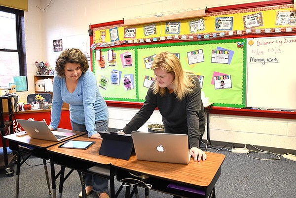 Kimberly Dalton, left and Kattie Cooper, third grade teachers at Crescent Elementary School. work up some learning material to share with their students by using google classroom during the coronavirus crisis.<br /> (Rick Barbero/The Register-Herald)