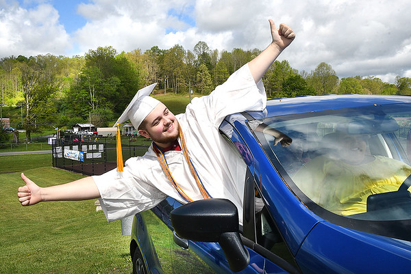 Titan Dunbar, of Liberty, celebrates his graduation ceremony from his car in the parking lot of the High School Friday morning. Parents stayed in their vehicles and drove their graduates up to a designated area where they were able to get out in groups of 10 to control the setting of no more than 25 individuals gathering at once. Parents were able to hear speeches through their radio by tuning into 107.7 The River.<br /> (Rick Barbero/The Register-Herald)