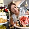 Candice, Meade, owner of Posh Manna Cake Art in Shady Spring, puts finishing touches on cakes she made for students graduating. <br /> (Rick Barbero/The Register-Herald)