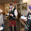 Willard Dean, volunteer, second from left, dressed as a pirate while delivering lunches, Anna Bowden, left, and Theresa Critchley and other residents at, Wildwood House Apartments on  Autumn Ln in  Beckley Thursday. Management at the appartments are doing differnt things to brighten residents days during COVID-19. One of the many things is dressing up every Thursday as a different character and delivering lunch door to door.<br /> (Rick Barbero/The Register-Herald)