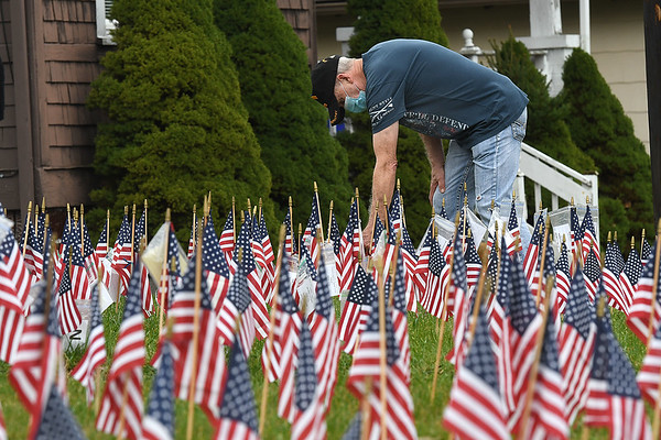 Jerry Rice, Vietnam Veteran, pulls up some flags for friends and family members during the Raleigh County Veterans Museum 7th annual Healing Fields Ceremony held at the museum off of Harper Road in Beckley Wednesday afternoon.<br /> (Rick Barbero/The Register-Herald)