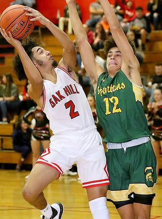 (Brad Davis/The Register-Herald) Oak Hill's Brandon Wisen drives to the basket as Greenbrier East's Bailee Coles defends Wednesday night in Oak Hill.