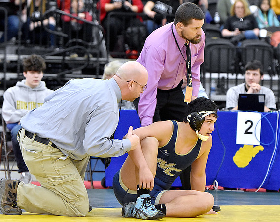 (Brad Davis/The Register-Herald) Nicholas County's Jacob WIlliams takes the opportunity to rest and strategize with coaches Craig Brake, right, and Kevin Amick during blood time in his match with Point Pleasant's Juan Marquez for the 195-pound championship Saturday night at the 73rd Annual State Wrestling Tournament in Huntington. Point Pleasant's Marquez won the match.