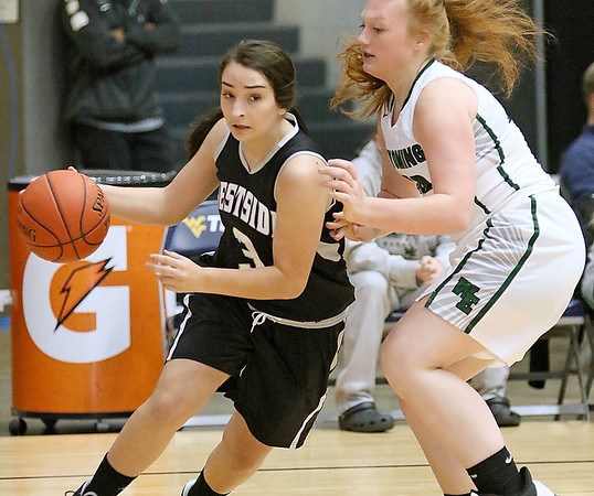 (Brad Davis/The Register-Herald) Westside's Hannah Toler drives along the baseline as Wyoming East's Sarah Saunders defends during Friday action at the New River Community and Technical College Shootout at the Beckley-Raleigh County Convention Center.
