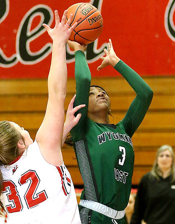 (Brad Davis/The Register-Herald) Wyoming East's Daisha Summers drives and scores as Oak Hill's Krista Shrewsberry defends Thursday night in Oak Hill.