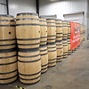 Annabelle Galyean checks out stacks of barrels at the West Virginia Great Barrel Company in Caldwell Monday. The first truckload of 53-gallon whiskey barrels made their way from the company and were delivered to Smooth Ambler Spirits Monday. (Jenny Harnish/The Register-Herald)