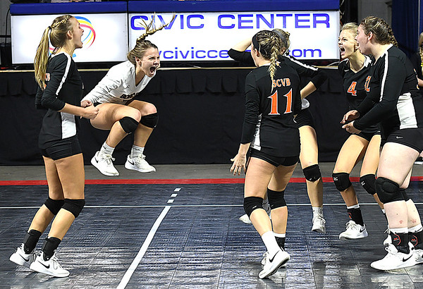 Liv Meador, second from left, of Summers Co., leaps to celebrates with her team after beating Greenbrier West 3 sets to 1 during the quarter-final match of the Girls State Volleyball Tournament held at the Charleston Civic Center Wednesday morning. <br /> (Rick Barbero/The Register-Herald)