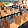 Katie Cooper, teacher at Crescent Elementary School, bags up materials belonging to her students for them to pick up at a later date. Students normally help, but could not because of COVID-19.<br /> (Rick Barbero/The Register-Herald)