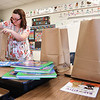 Kayla Armstrong, first grade teacher at Crescent Elementary School, bags up materials belonging to her students for them to pick up at a later date. Students normally help, but could not because of COVID-19.<br /> (Rick Barbero/The Register-Herald)