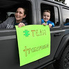 Trish Freemans, left, and her son Cayson, 9, of Beckley, displays a message as they make a brief stop in a parade of cars past, Tammy Evans, of Beckley, home on the corner of, Park Ave. and Third Ave., Family and friends celebrated with a parade of 14 cars and two fire trucks the one year anniversary of her daughter, Shannon Barbero, of Prosperity, donating half her liver to save her mothers life. Evans, who suffered from NASH, nonalcoholic steatohepatitis, stood her distance because of COVID-19, was surprised and said, how many people can say they had their own parade?<br /> (Rick Barbero/The Register-Herald)
