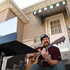 Matt Mullins, with the Bringdowns band, live streams a stomg from his front porch on Prince Street in Beckley.<br /> (Rick Barbero/The Register-Herald)