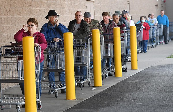 Large line of people wait between shopping carts avoiding close contact to enter Sam's Club in Beckley Tuesday morning.<br /> (Rick Barbero/The Register-Herald)