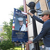 Glen Peterson, volunteer, hangs one of thirty one military banners that was placed throughtout the city to honor local veterans & active-duty service members. These were placed for Memorial Day and will remain on display up till the first week of June. Flags will go back up in November for Veterans Day with hopes to add additional forty four more displaying on all seventy five poles in the downtown area.<br /> (Rick Barbero/The Register-Herald)