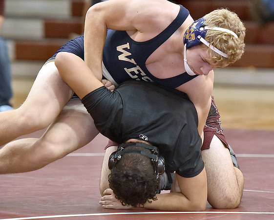 (Brad Davis/The Register-Herald) Greenbrier West's John Parks takes on Woodrow Wilson's Kenneth Farmer Jr. in a 170-pound weight class matchup Saturday morning at Woodrow Wilson High School. West's Parks won the match.