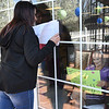 Melissa Blair, left, and her mom, Thelma james, communicate through a window at Harper Mills Nursing Home in Beckley Saturday morning with sign messages. Her mom is not allowed visitors inside because of the coronavirus.<br /> (Rick Barbero/The Register-Herald)