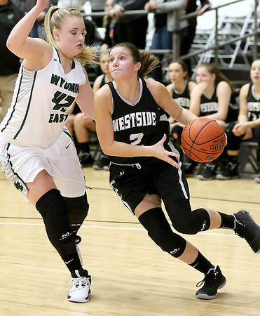 (Brad Davis/The Register-Herald) Westside's Leslie Bailey drives along the baseline as Wyoming East's Hannah Blankenship defends during Friday action at the New River Community and Technical College Shootout at the Beckley-Raleigh County Convention Center.