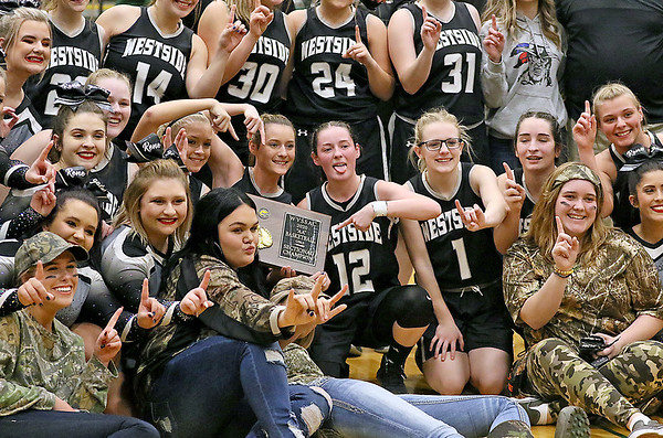 (Brad Davis/The Register-Herald) Students and cheerleaders join their Westside classmates on the court to celebrate with the trophy after defeating Wyoming East for the Region 3, Section 1 championship Wednesday night in New Richmond.