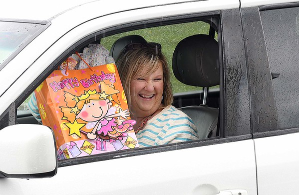 Jaimi Hughes, of Beckley, presents a gift through her car for Charlee Roop's first birthday. She attended the drive-through party at Matt and Jenna's house in their driveway off of Grandview Road in Beaver Saturday afternoon because of COVID-19. <br /> (Rick Barbero/The Register-Herald)
